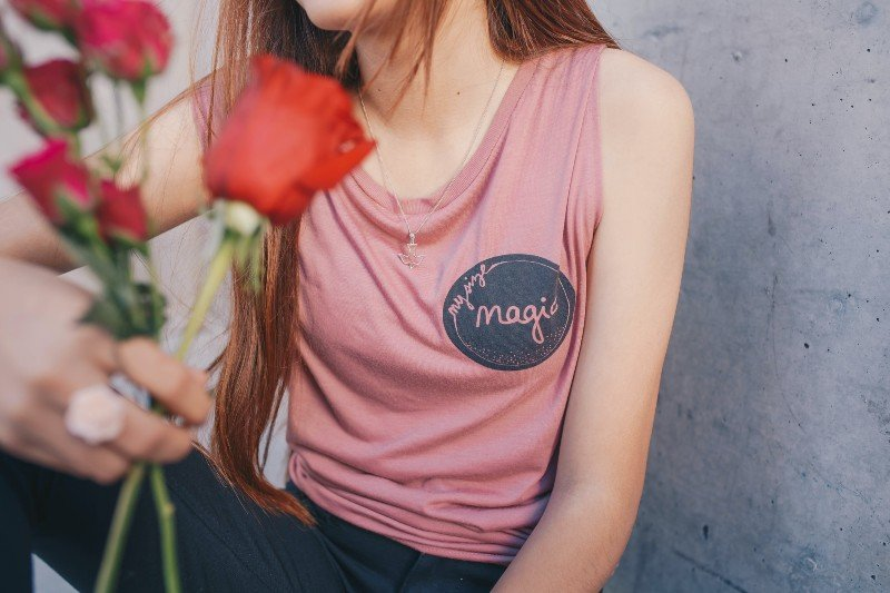 What is body neutrality? A red haired woman is holding a bunch of red roses.